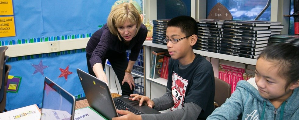 Teacher assisting student at computer